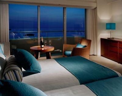 客船をイメージした白×ブルーの客室。窓からは万座の海が一望できる