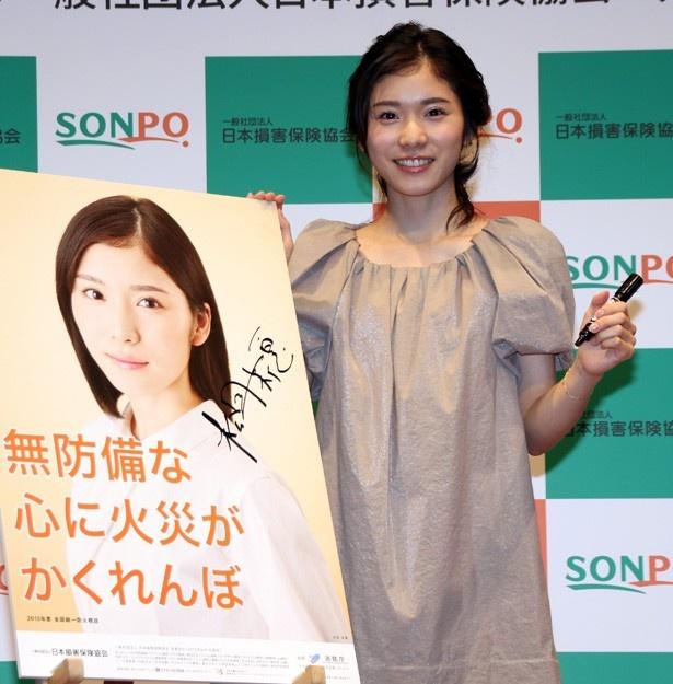 松岡茉優は防火ポスターにサインを入れ笑顔を見せる