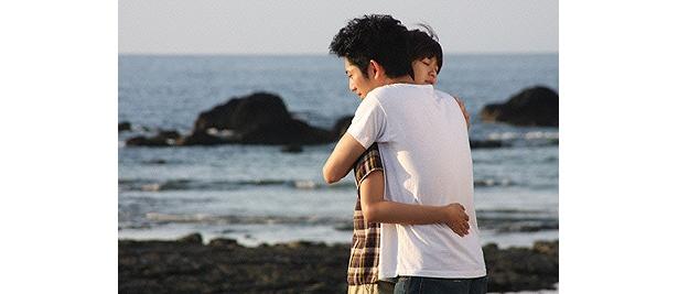 海岸で互いに抱きしめあうふたり