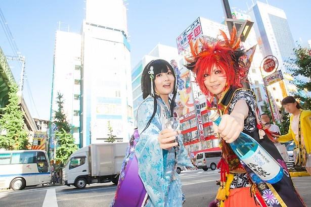 【写真を見る】秋葉原の街中を、日本酒片手に探索するコスプレ姉妹、仁王