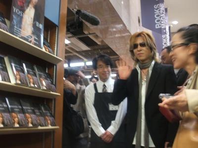 自身の本の陳列前でファンに手を振るYOSHIKI