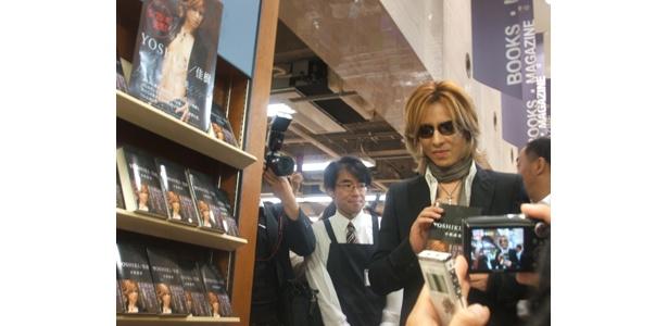 自身の本の陳列前で本を手にほほえむYOSHIKI