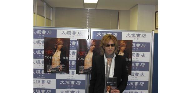 囲み取材で、本を手に撮影に応えるYOSHIKI