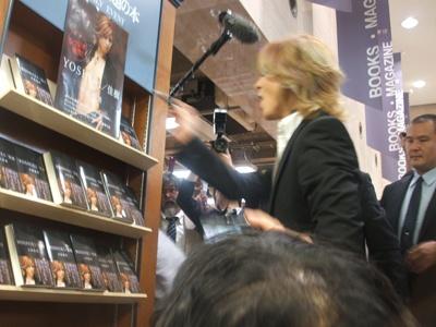 自身の本の陳列前でポスターにサインするYOSHIKI