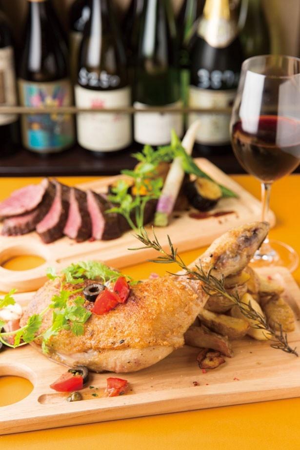 各地の国産ワインがそろう青山バル。グラスワインは510円~用意する。「日向鶏の骨付きもも肉のグリル」(手前)と「山形牛A4ランクうちもも肉」(奥)はボリューム満点!
