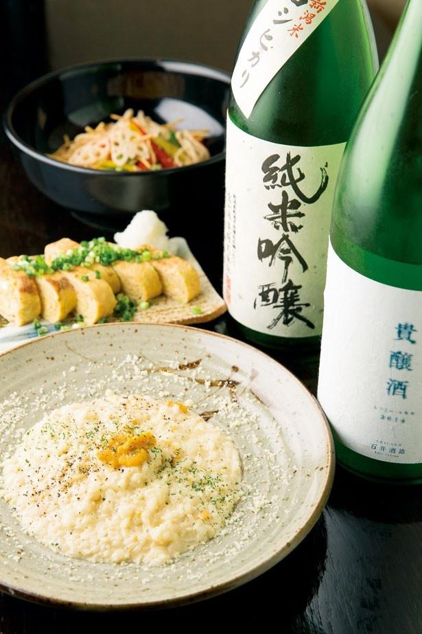 sakebaのスタッフ一同がおすすめする、食用米を使った甘口の日本酒「宝山」(写真右奥、グラス830円)。「和食屋さんの生うにクリームリゾット」(写真手前、1280円)も美味!