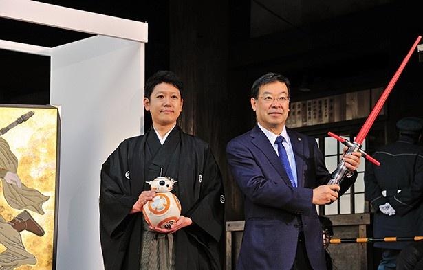 【写真を見る】ライトセーバーを持つ山田啓二京都府知事(写真右)とBB-8のフィギュアを持つ山本太郎さん(同左)