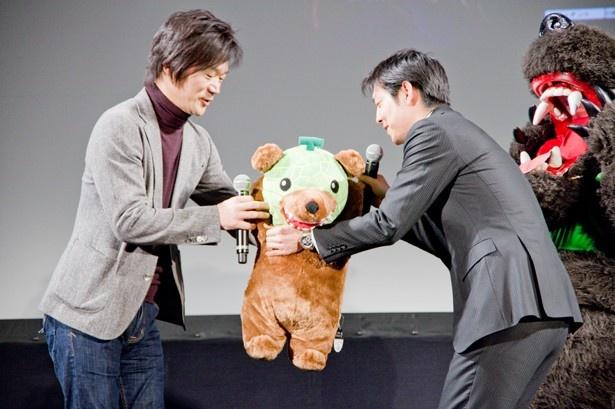 【写真を見る】鈴木市長からかわいい夕張メロン熊のぬいぐるみをプレゼントされるジェシー代表