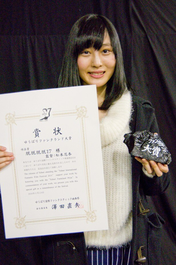 賞状と石炭のトロフィーを手にした『脱脱脱脱17』の松本花奈監督