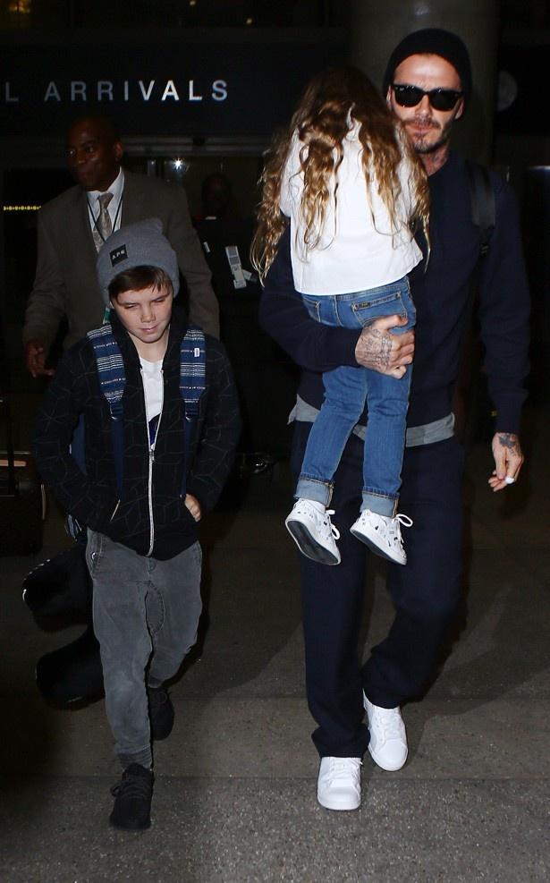 娘のハーパーを抱いて歩くデビッド・ベッカム