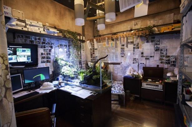 大きな水槽が置かれたカエル男の部屋。PCには監視カメラの映像が映しだされている