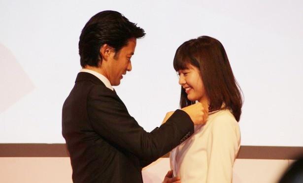 桝田沙也香アナウンサーも竹野内豊からバッチを着けてもらうことになり、思わず笑顔がこぼれる