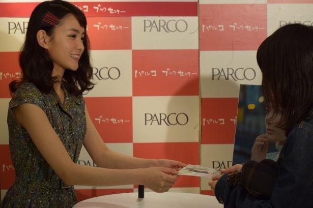 女性ファンにサイン入りのカレンダーを手渡し