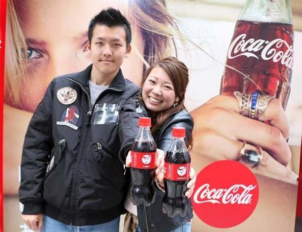 「コカ・コーラ」スタンプボトルを受け取った来場者。男性は「彼女に気持ちを伝えるときに使えそう!」とニッコリ