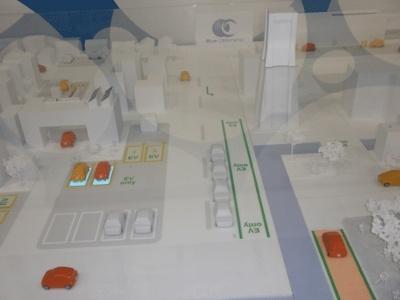 電気自動車が走る、未来都市のジオラマ。左に2台、充電中の車がありますね