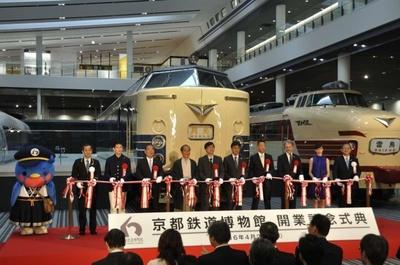 京都鉄道博物館開業記念式典のテープカットの模様。京都市の門川大作市長や俳優の西村和彦さんらもお祝いに駆けつけた。左端は同館の公式キャラクター・ウメテツ