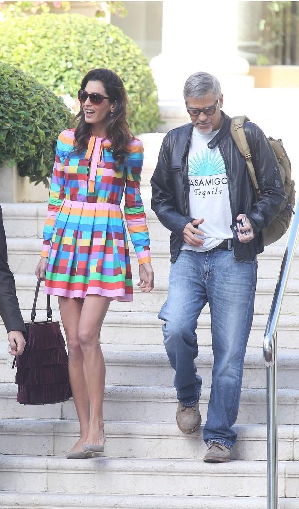 カラフルなミニ丈のワンピースで夫のジョージと歩くアマル・クルーニー