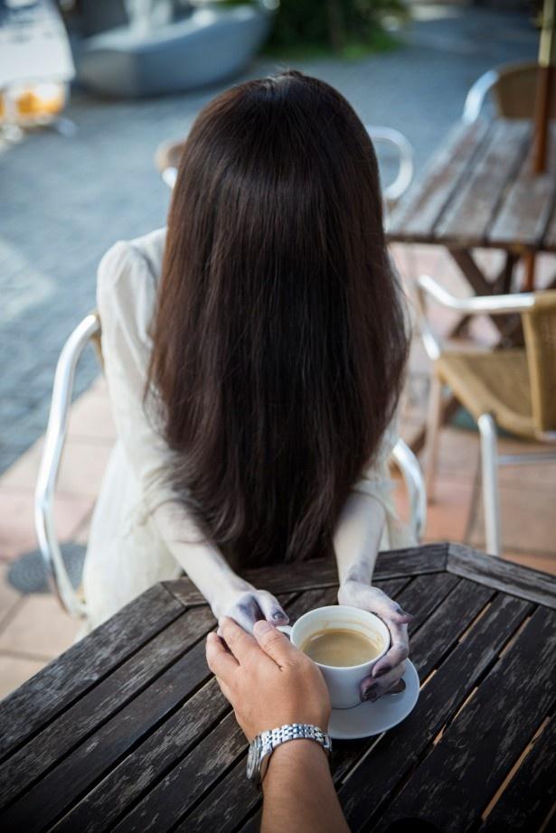 冷たい手をコーヒーで暖める貞子