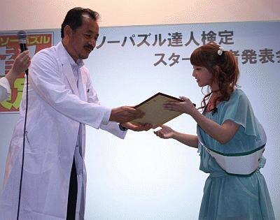 ジグソーパズル検定委員会委員長から達人認定証を授与される矢口さん