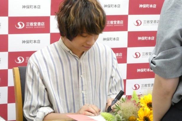 イベントに参加したファンにサインをして本を手渡す尾崎