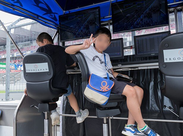 ピットウォーク中、レース時に監督やレースエンジニアがチームに指示する場所に座る子供も