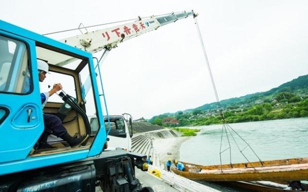 重さ1tの手こぎ舟をクレーンでつり上げて川に下ろす。これも船頭の仕事だ