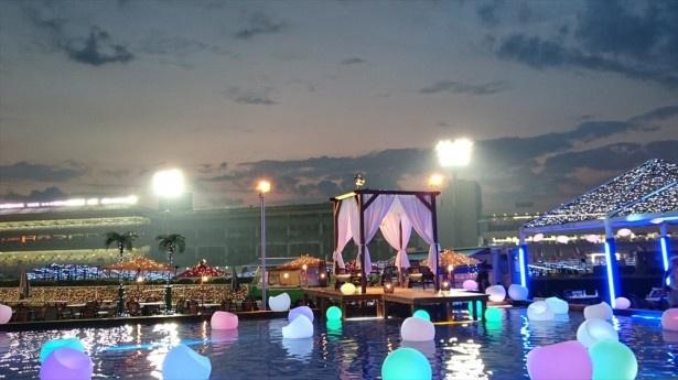 【写真を見る】ライトアップされた水上コテージが会場を彩る