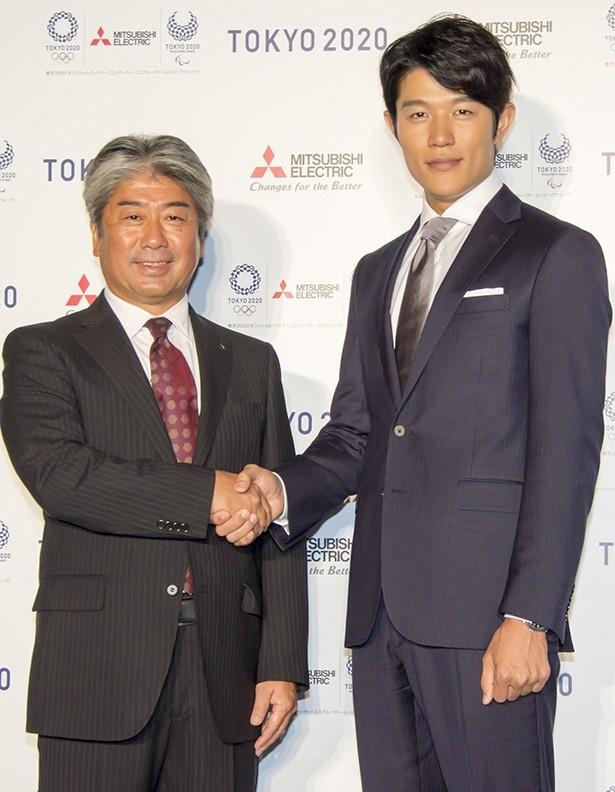 自身もバスケットボールで活躍していたという鈴木亮平は身長186cm。三菱電機株式会社関邦彦宣伝部長と握手