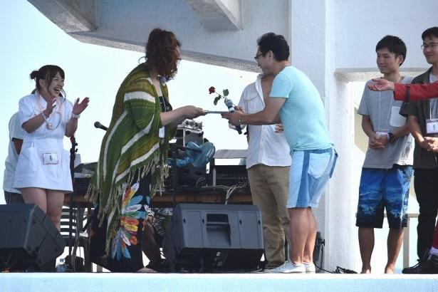 杉山清貴が、CHARAの「やさしい気持ち」を歌って優勝したBig mama(エントリーネーム)さんに目録を渡す