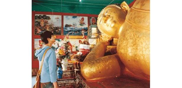 寝仏を見つめる伽奈。タイでの生活にも慣れてきたところか
