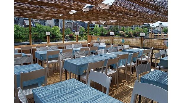 約60人まで入れる川床席。わわやかな青のテーブルクロスが印象的/お食事処 山とみ