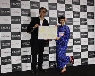 森美術館館長の南條史生さん(左)と、「パステル宇宙」をイメージして自身がデザインした絵画を持つ篠原さん