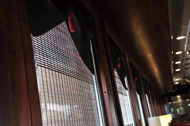 大名籠をイメージした窓のあしらい。カーテンも木製のすだれ風でおしゃれだ/京都丹後鉄道 丹後くろまつ号