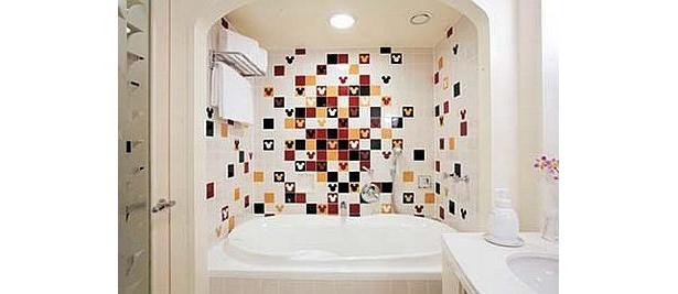 黒・赤・黄色のカラフルなミッキーフェイスが、バスルームの壁のタイルにちりばめられている