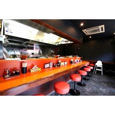 【極濃麺家初代 一本氣】黒い壁に映えるオレンジのカウンターとイス。お店のメルマガメンバーになれば、裏メニューなどお得な情報も