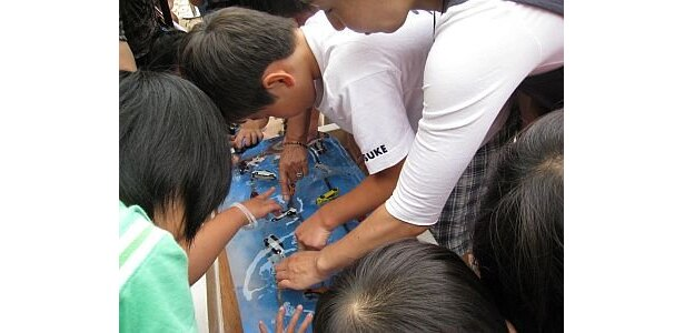 手で氷を溶かそうと奮闘する子供たちの画像