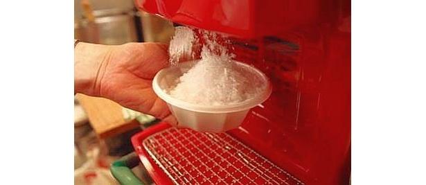 ダシと熱々のたこ焼きが入った器の上に、シャーッと氷をのせ…