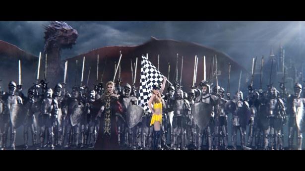 レースクイーン姿で戦士たちの中心でポーズを決める