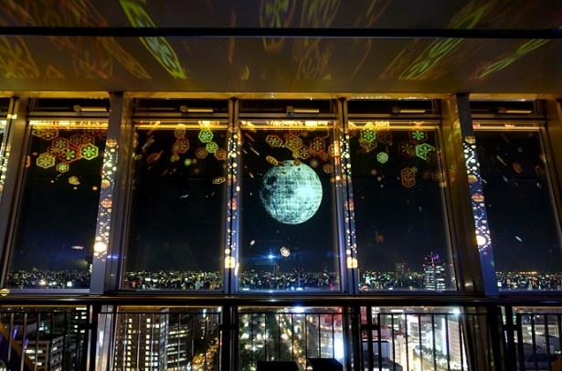 名古屋の夜景に、月を中心とした幻想的な映像が重なる