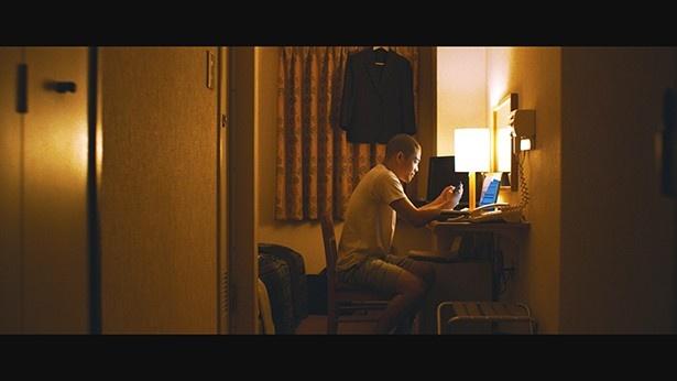 「子供の誕生日を一緒に過ごせず、出張先のビジネスホテルで寂しく動画を見る」というシーン