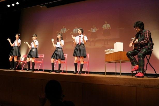 """倉本美津留""""校長""""(右)のギターで歌う岡田愛、日高麻鈴、森萌々穂、倉島颯良(左から)"""
