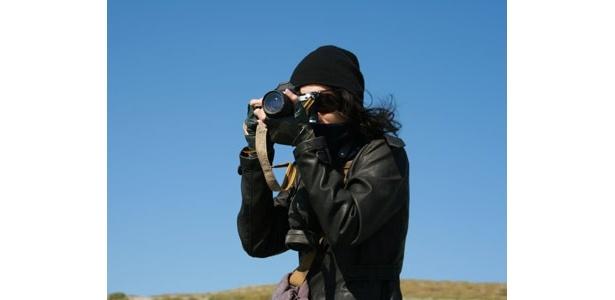 砂漠の真っ只中でカメラを構える綾野