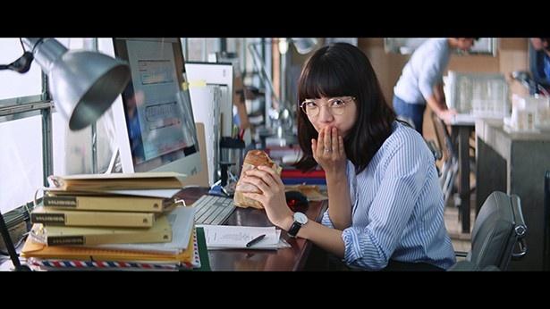 【写真を見る】仕事しながらのランチを上司に見つかり恥ずかしそうな小松菜奈