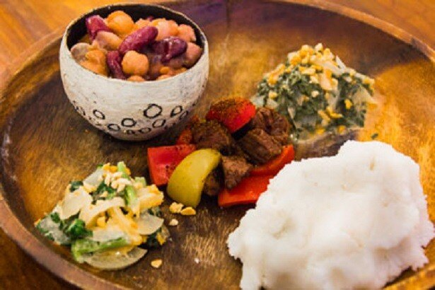 トウモロコシの粉から作る「シマ」というザンビア伝統の主食に、葉野菜のピーナッツ和え、豆のトマト煮込み、シチューがついた「ザンビアプレート」(500円)