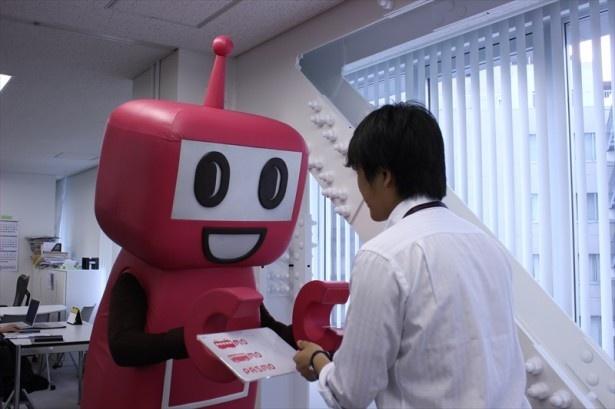 【写真を見る】相手の目を見てしっかり名刺交換するPASMOのロボット。カメラ目線ではない。