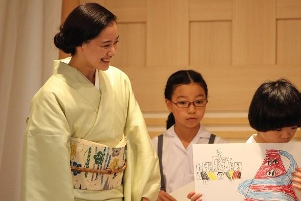 児童たちの絵を見つめる蒼井優さん