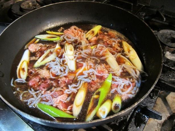 秘伝のだしに醤油、みりん、酒、砂糖を加えてすき焼きの具材を煮込む