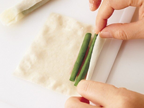 春巻きの皮の手前に具をのせたら、きつめに巻いていき、端を閉じます。揚げ焼きにしたときにくずれるのを防ぐコツ。