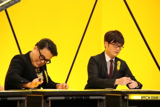 必死にボタンを連打するとろサーモン・久保田和靖(左)