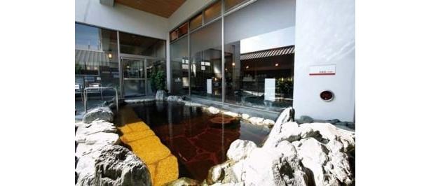 天然温泉 満天の湯の「岩風呂」。施設の地下から湧く褐色の温泉を楽しめる露天の天然温泉